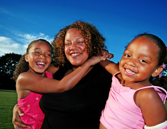 an image of a black woman and her two young girls smiling for a photograph